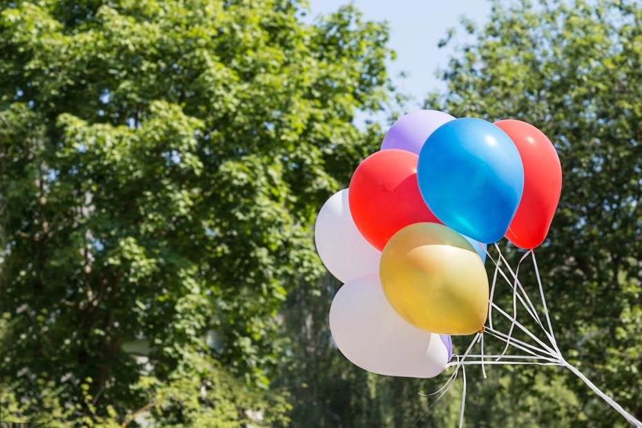 A bunch of balloons filled with helium on the background of nature