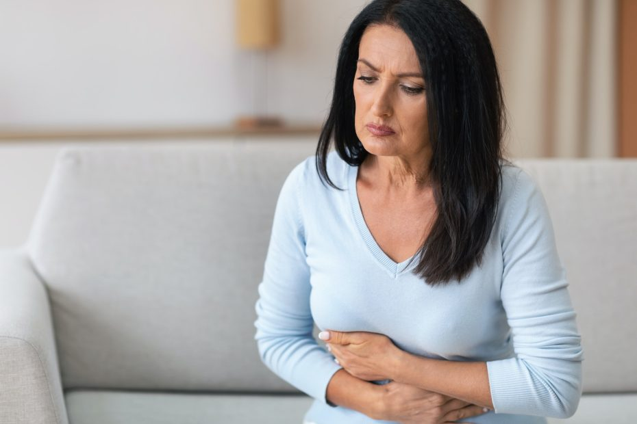 Mature Woman Suffering From Stomachache, Touching Belly